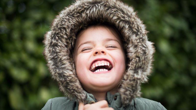 Barn med lurvig luva skrattar